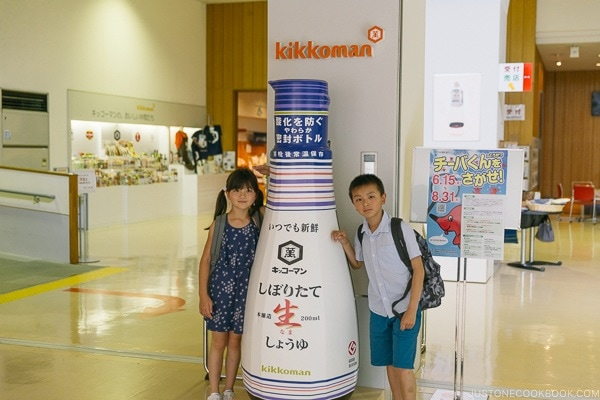 children next to a giant soy sauce bottle at Kikkoman Factory in Noda Japan | Kikkoman Factory Tour - justonecookbook.com