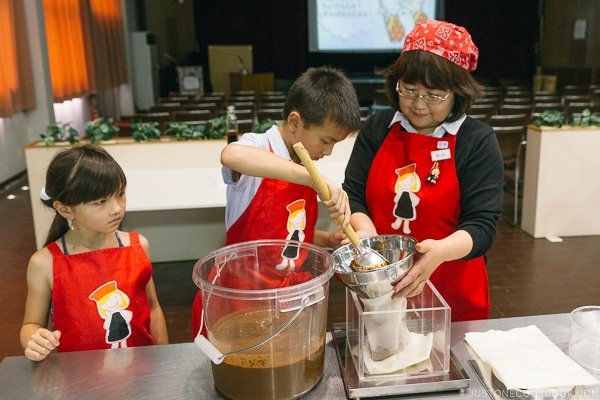 children scooping soy sauce raw mixture into bag for pressing at Kikkoman Factory in Noda Japan | justonecookbook.com