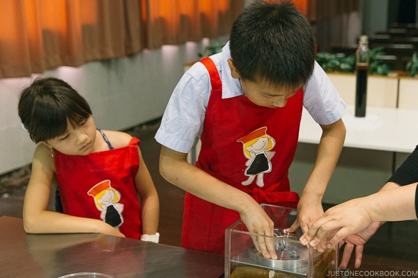 children pressing weight on fabric soaked in soy sauce at Kikkoman Factory in Noda Japan | justonecookbook.com