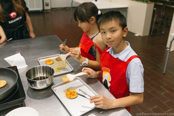 children brushing soy sauce on rice cracker at Kikkoman Factory in Noda Japan | justonecookbook.com