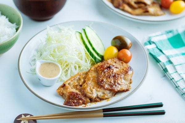 A white plate containing thinly sliced Miso Ginger Pork served with shredded cabbage, sliced cucumbers, and cherry tomatoes.