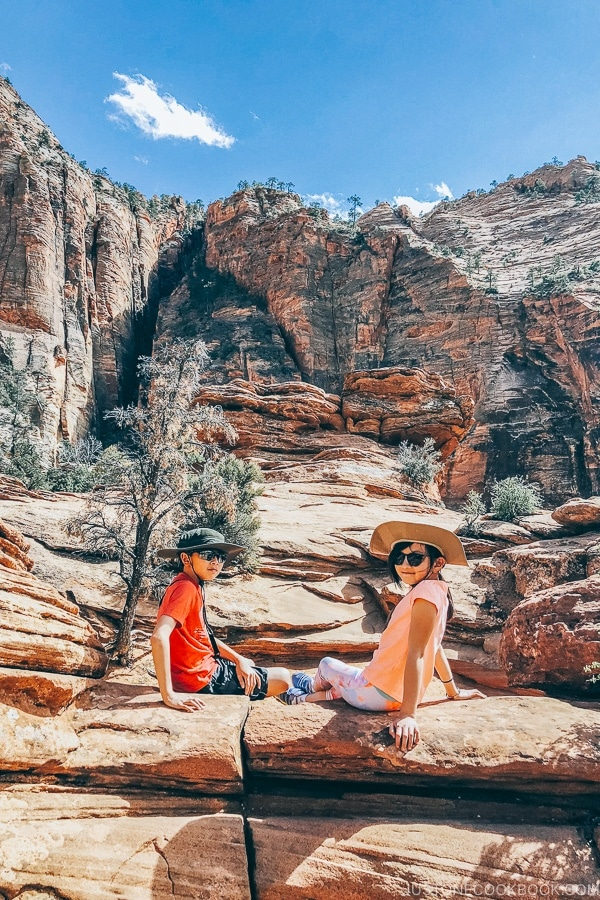 children sitting on rocks at the end of the Canyon Overlook Trail - Zion National Park Travel Guide | justonecookbook.com