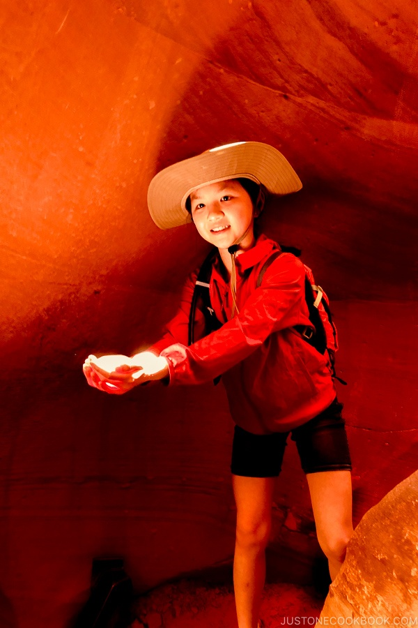 child holding a beam of light next to sand rock formation - Lower Antelope Canyon Photo Tour | justonecookbook.com