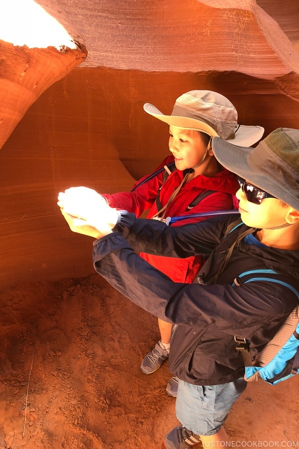 children with a beam of light shining at their hands - Lower Antelope Canyon Photo Tour | justonecookbook.com