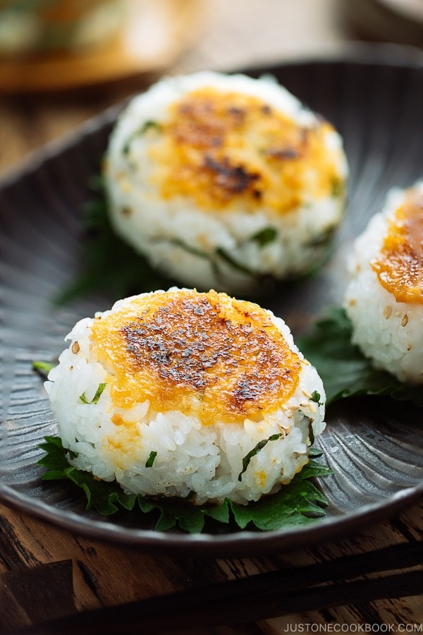 A black dish containing miso flavored Yaki Onigiri (Grilled Rice Balls) garnished with shiso leaves.