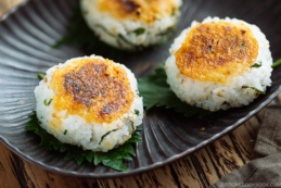 A Japanese bizenware containing miso flavored Yaki Onigiri (Grilled Rice Balls) garnished with shiso leaves.