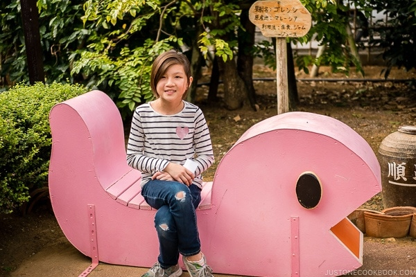 child sitting on wooden sculpture - Okinawa World | justonecookbook.com