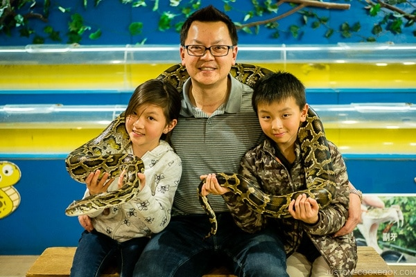A man with two children with a snake wrapped around them