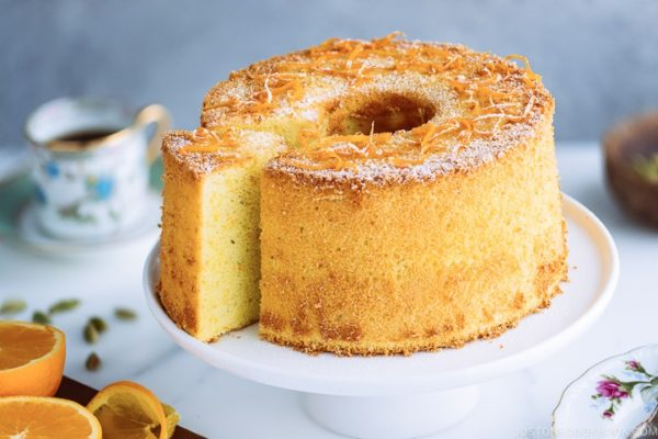 Orange Chiffon Cake on top of the cake stand. Chiffon cake has a hint of cardamom and powder sugar dusted on top.