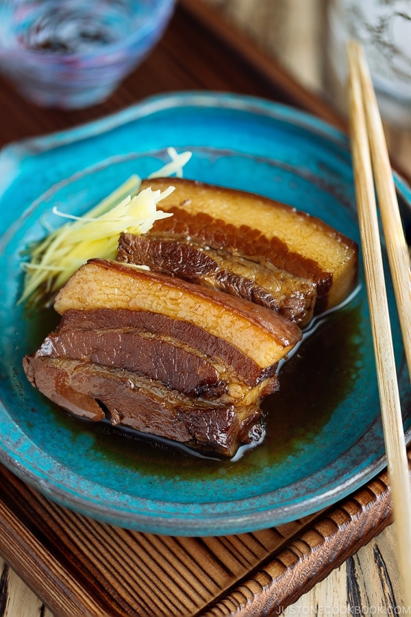 A blue plate containing 2 slices of Rafute (Okinawan Braised Pork Belly) garnished with julienned ginger.
