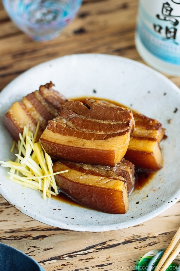 A white plate containing 3 slices of Rafute (Okinawan Braised Pork Belly) garnished with julienned ginger.
