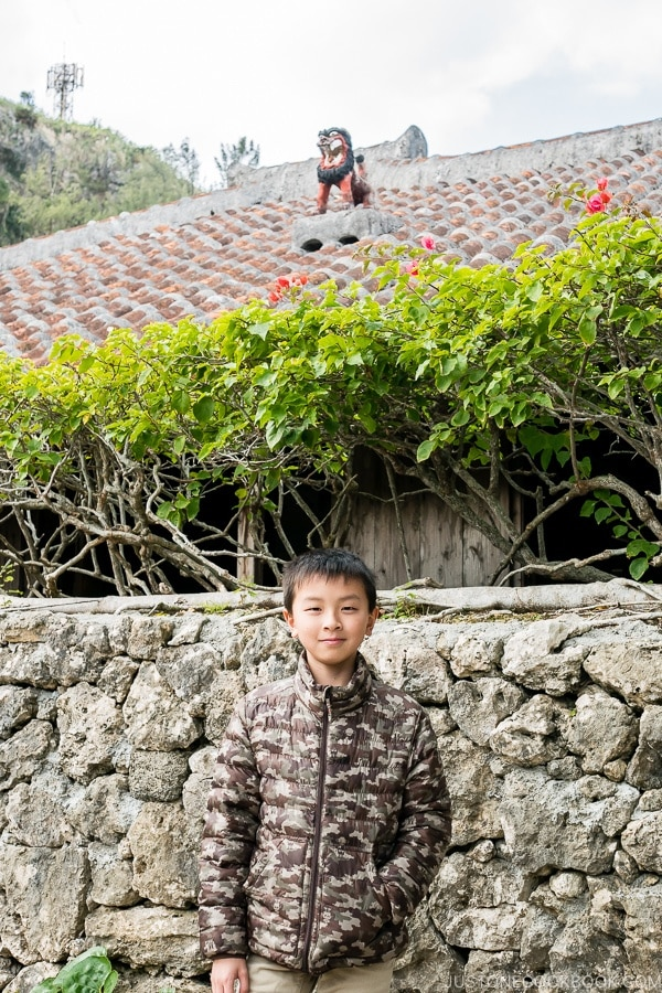 child in front of a traditional ryukyu house at Ryukyu Mura Okinawa | justonecookbook.com