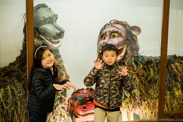 children in front of shisa figures at Ryukyu Mura Okinawa | justonecookbook.com