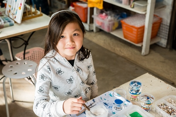 child looking at camera sitting in front of art craft at Ryukyu Mura Okinawa | justonecookbook.com