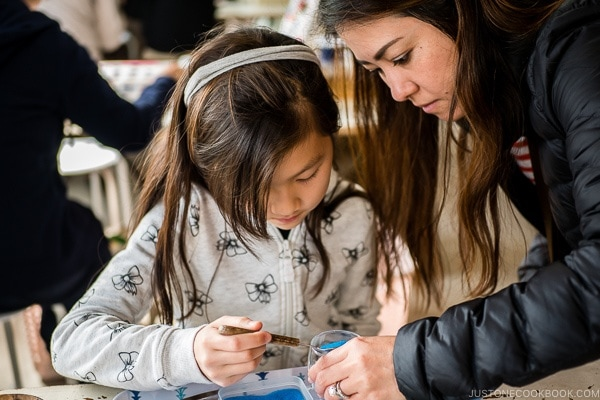 Nami helping child with art craft at Ryukyu Mura Okinawa | justonecookbook.com