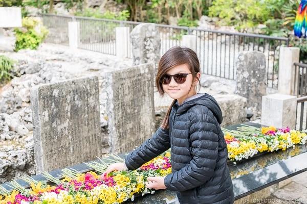 child dedicating flower at Himeyuri Peace Museum - Okinawa Travel Guide | justonecookbook.com
