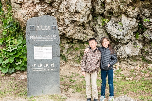 Just One Cookbook children standing next to world heritage sign at Nakagusuku Castle - Okinawa Travel Guide | justonecookbook.com