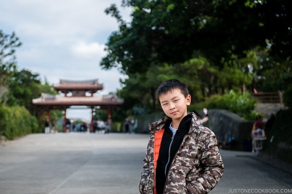 child at Shuri Castle with Shureimon Gate in the background - Okinawa Travel Guide | justonecookbook.com