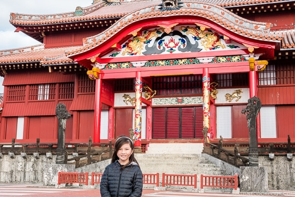 child in front of restored Shuri Castle Seiden - Okinawa Travel Guide | justonecookbook.com