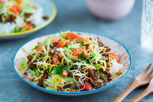 Okinawa Taco Rice on a colorful plate consisting of white rice, taco seasoning ground beef, shredded lettuce and cheese, topped with tomato salsa.