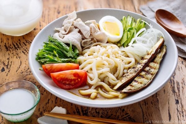 Cold Curry Udon served with thinly sliced pork, grilled eggplant, boiled egg, cucumber, and tomatoes in a chilled curry sauce.
