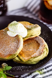 Matcha Souffle Pancakes topped with powder sugar and fresh whipped cream.