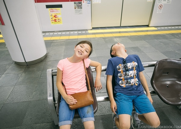 Just One Cookbook children exhausted sitting on bench in Shinjuku Station - Shinjuku Travel Guide | justonecookbook.com
