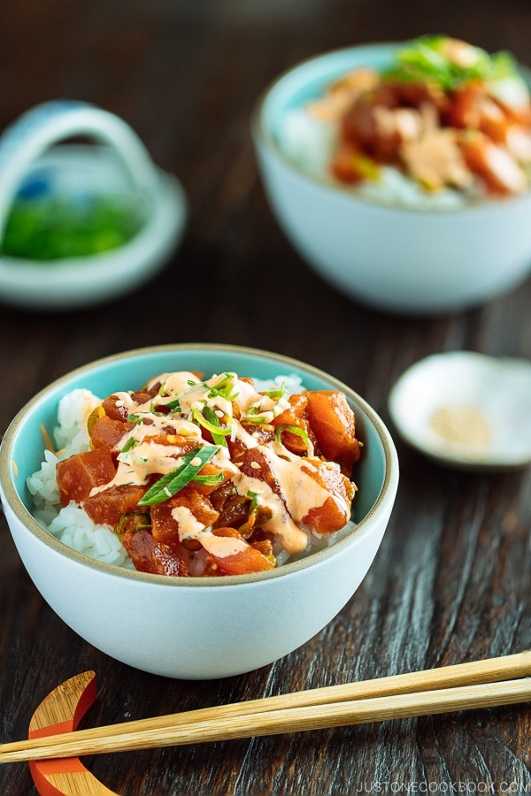 Spicy Tuna served over bed of rice in a bowl, drizzled with spicy mayo and garnished with scallion on top.