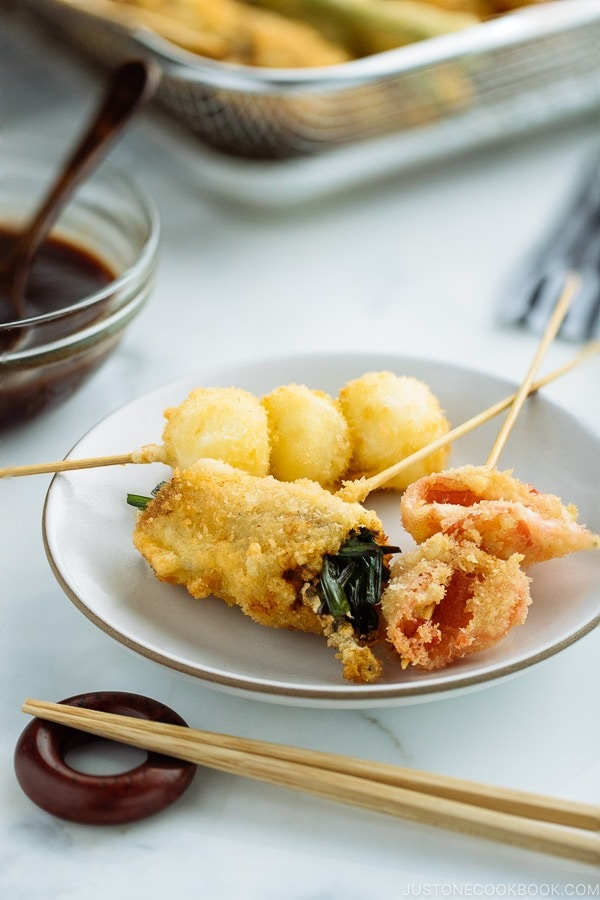 A white plate containing golden and crispy Kushikatsu (Kushiage) served with savory sauce.