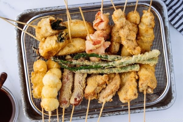 Wire basket containing golden and crispy Kushikatsu (Kushiage) served with savory sauce.