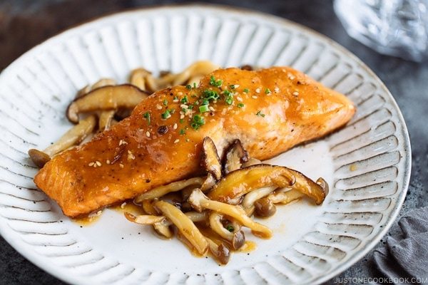 White plate containing Miso Butter Salmon served with sauteed shiitake and shimeji mushrooms.