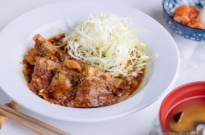Pan Fried Ginger Pork Belly served with thinly shredded cabbage.