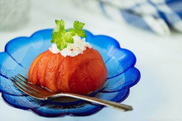 A blue glass containing Japanese-style Pickled Tomatoes garnished with minced onion.