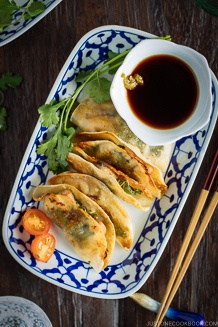 A plate containing chicken shiso gyoza and a small bowl of ponzu and yuzu kosho.