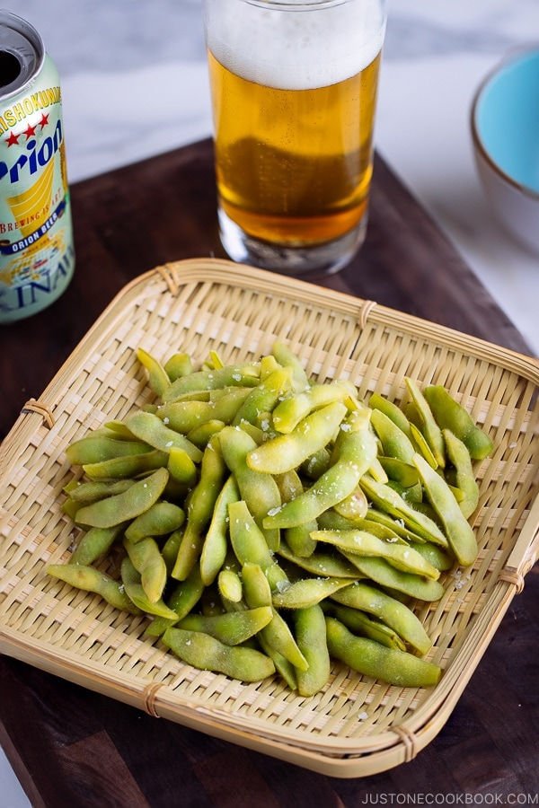 Edamame served in bamboo basket and beer glass in the back.