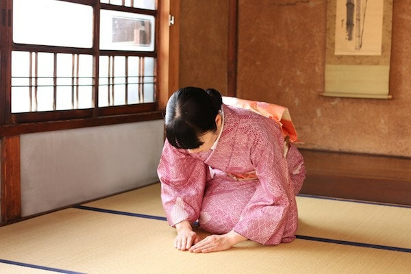 Lady in Kimono bowing on tatami room.