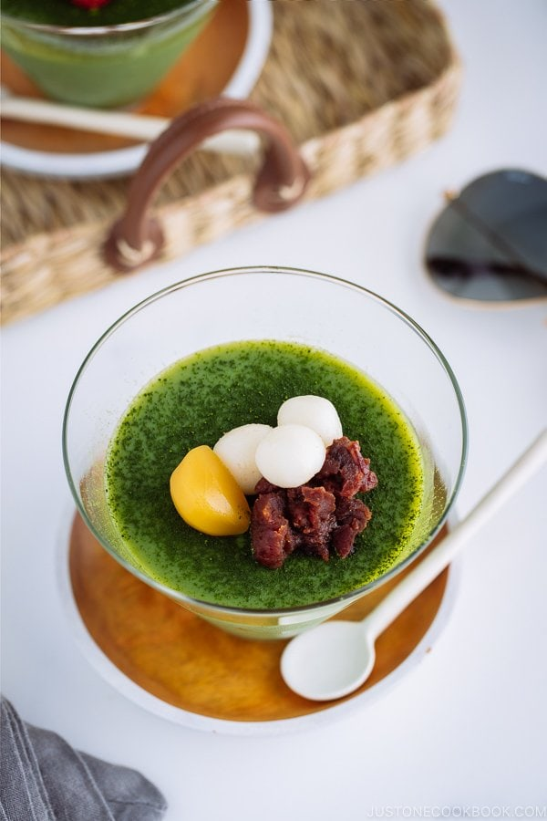 Matcha Vegan Panna Cotta served in a glass bowl, topped with mochi, red bean paste, and candied chestnut.