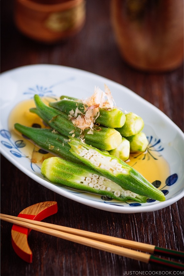 Japanese white and blue plate containing Japanese style okra salad topped with bonito flakes.