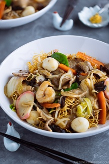A plate containing Chinese-style crispy noodles with saucy seafood and vegetables.