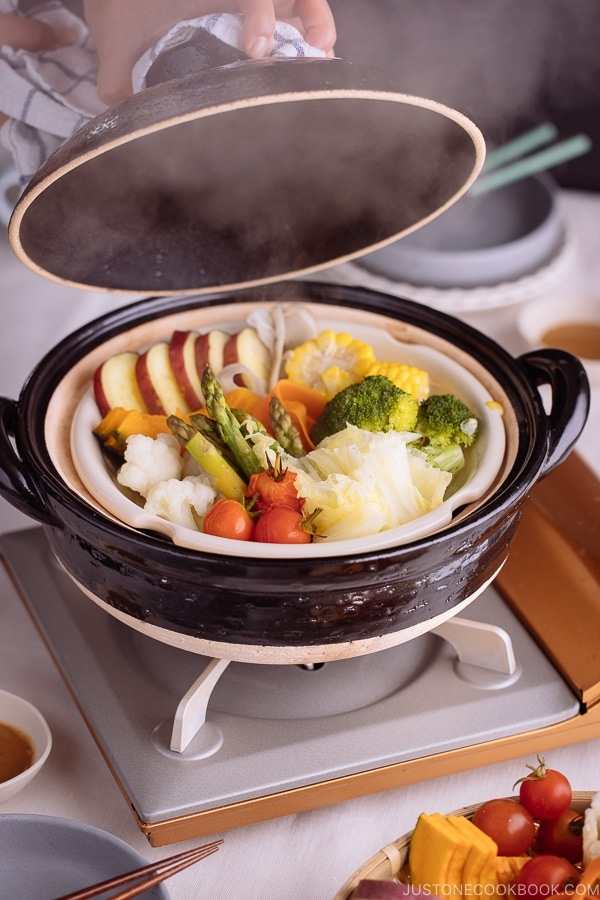 Steamed vegetables in a Japanese earthenware pot, donabe. Steam coming off from the pot.