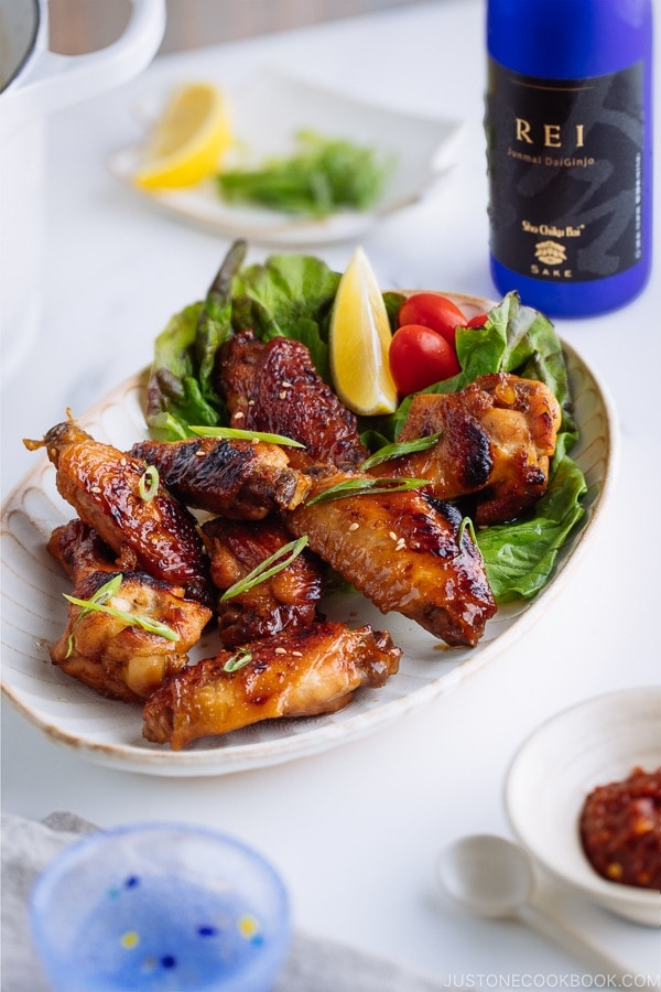 Teriyaki wings served on a white plate garnished with lemon, tomatoes and green lettuce.