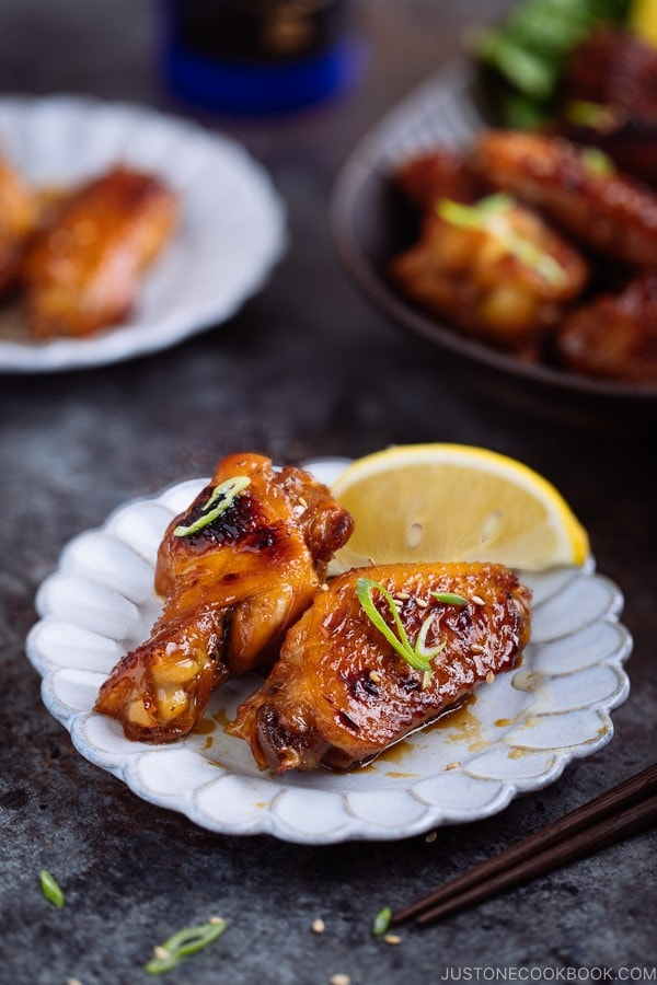 Teriyaki wings served on a white plate garnished with green onion and sesame seeds.