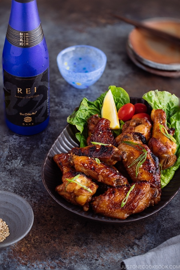 Teriyaki wings served on a dark brown plate garnished with lemon, tomatoes and green lettuce.