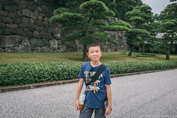 A boy standing in front of a tree