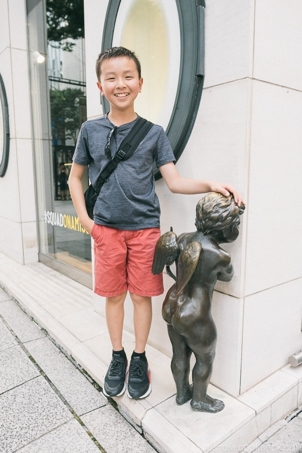 Just One Cookbook child standing next to cupid statue in front of Tenshodo Ginza - Tokyo Ginza Travel Guide | www.justonecookbook.com