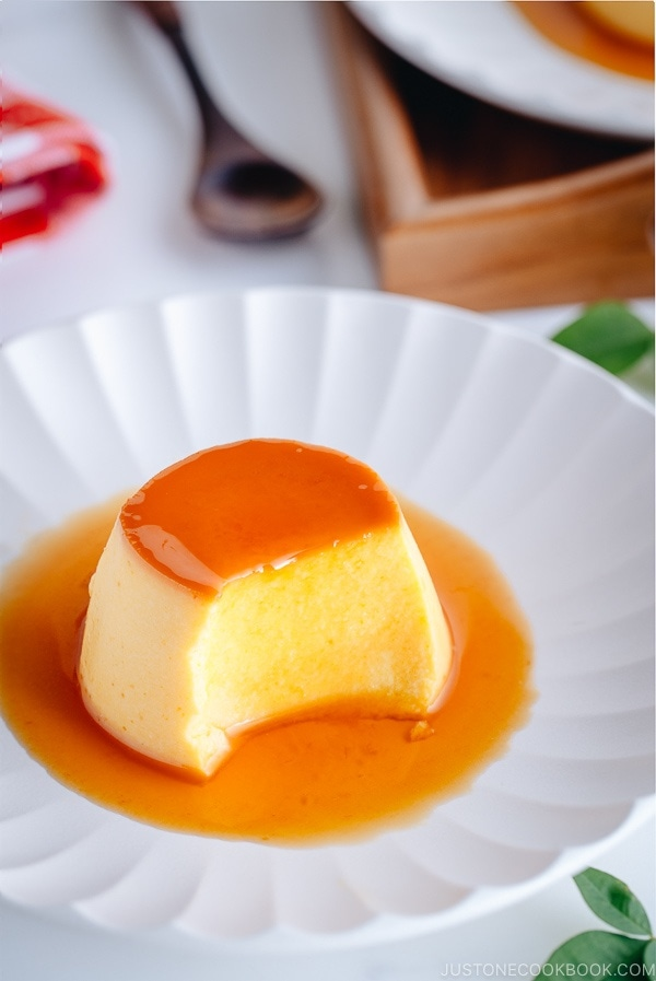 A white plate containing Kabocha-flavored Flan with caramel sauce on top.
