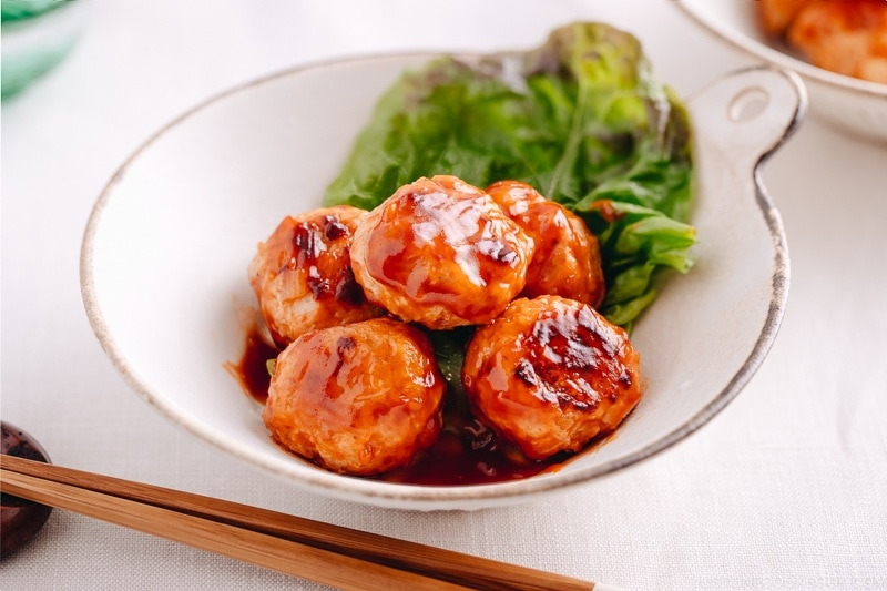A white dish containing Chicken Meatballs with Sweet and Sour Sauce.