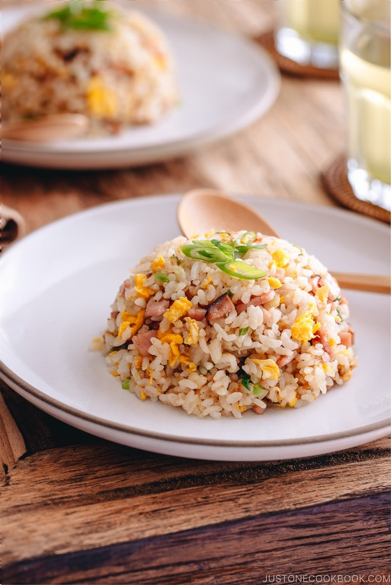 Fried rice with egg, ham, and green onion on a white plate.