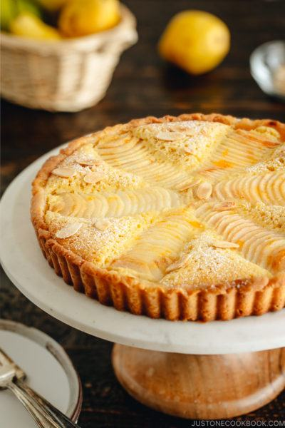 Pear and Almond Tart (Pear Frangipane Tart) is on the cake stand. The tart is dusted with powdered sugar and sprinkled with toasted almond slices.
