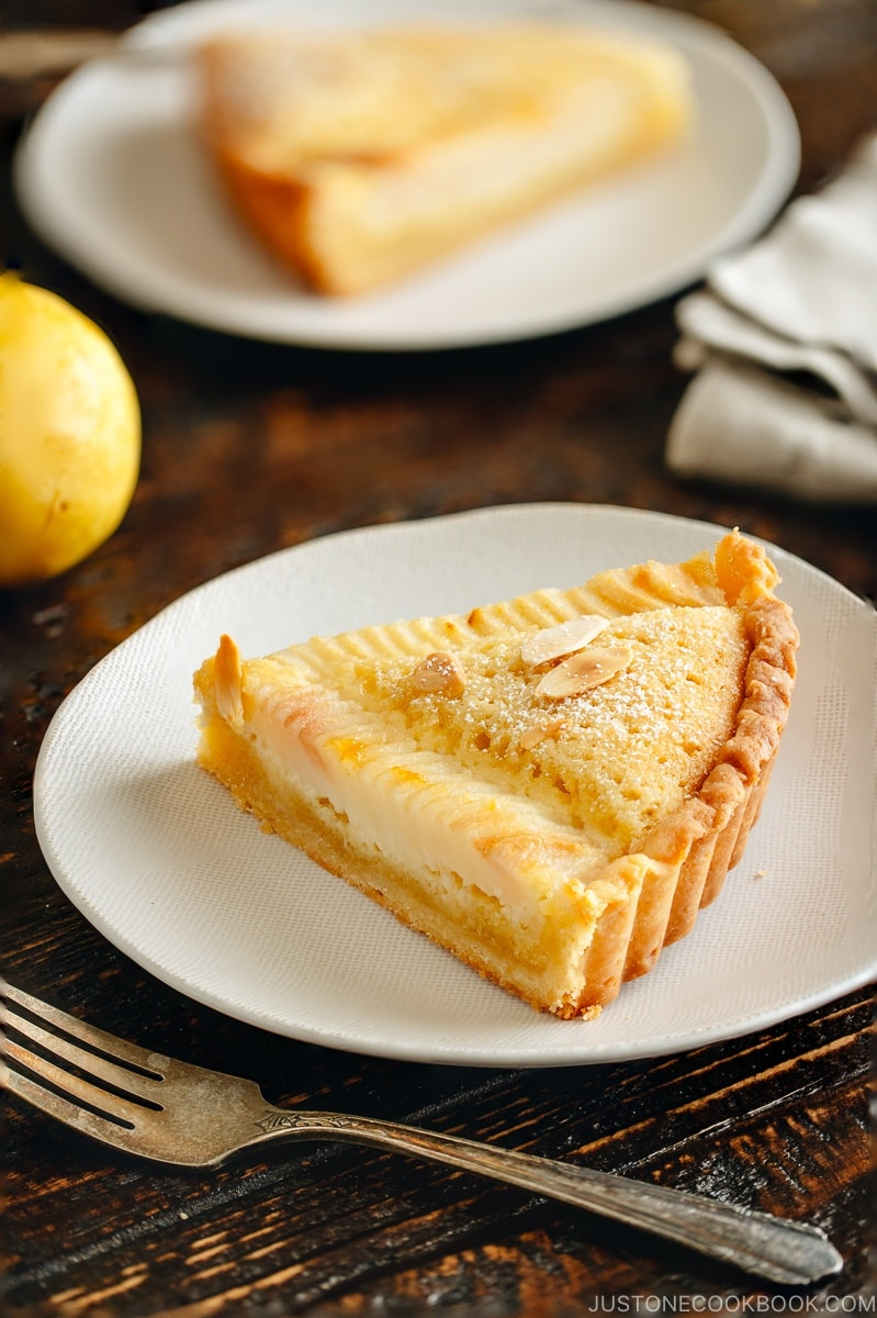 A slice of Pear and Almond Tart (Pear Frangipane Tart) on a plate.